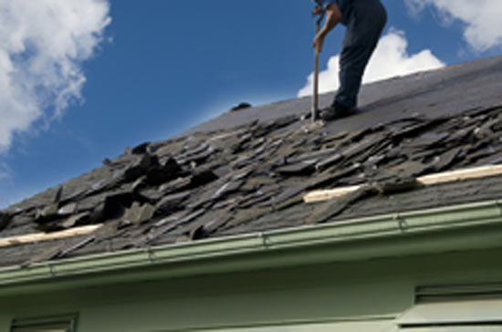 Roofer cleaning off old roofing shingles revealing roofing felt underneath